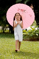 Girl walking in a park with an umbrella