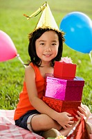 Portrait of a girl with holding a stack of birthday gifts and smiling in a park