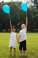 Girl with a boy standing in a park and holding balloons