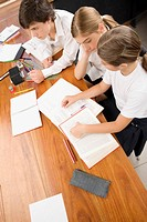 High angle view of two schoolgirls and a schoolboy studying in a classroom