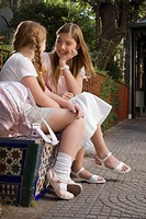 Two schoolgirls sitting on a bench and looking at each other