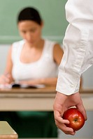Close_up of a person's hand holding an apple with a female teacher sitting in the background