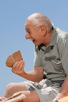 Close_up of a senior man playing cards