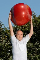 Portrait of a senior man exercising with a fitness ball