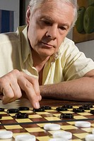 Close_up of a senior man playing checkers