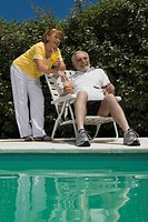 Senior couple holding glasses of juice at the poolside