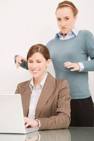 Businesswoman working on a laptop with her colleague try to strangling behind her