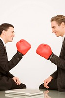 Side profile of two businessmen wearing boxing gloves