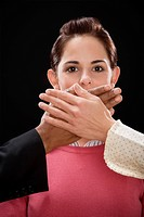 Close_up of a person's hand covering a businesswoman's mouth