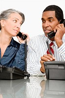 Businessman and a businesswoman talking on landline phones