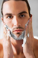 Portrait of a young man applying shaving cream on his face