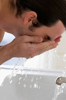 Close_up of a young man washing his face