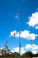 Low angle view of totonac voladores flying dancers flying from the pole, El Tajin, Veracruz, Mexico