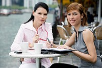 Portrait of two businesswomen sitting at a sidewalk cafe