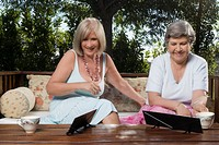 Two women sitting on a couch and playing mahjong