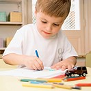 Close_up of a boy drawing on a sheet of paper