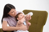Mid adult woman feeding her son with a baby bottle and smiling