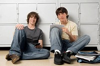 Portrait of two high school students sitting in front of lockers