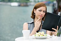 Businesswoman looking at a ring binder at a sidewalk cafe