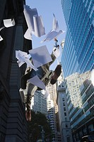 Low angle view of a businessman jumping and throwing papers