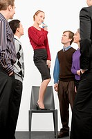 Businesswoman standing on a chair and blowing whistle with business executives standing beside her
