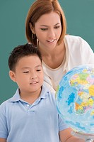Female teacher with her student looking at a desktop globe