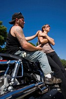 Young man, on his motorcycle, with a young woman