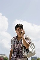 Young woman talking on a mobile phone and smiling