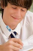 Close_up of a high school student writing in a notebook