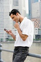 Side profile of a mid adult man text messaging and smiling