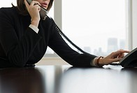Woman dialing telephone in office