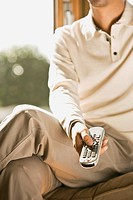 Man sitting on chair with remote control