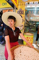 Woman selling hung yan bang, almond flavored cookies, a favorite in Macau, Macau, China, Asia