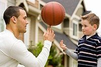 man (age 25) teaching boy (age 6) to spin basketball on fingers