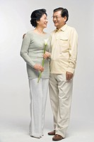 Senior couple holding flower