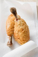 Two breaded chicken legs on paper