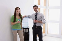 Co_workers smiling by water cooler