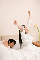 Husband sleeping by wife stretching herself