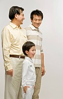 Grandfather, father and grandson standing together with smile