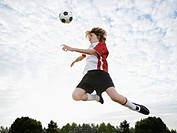 Boy jumping toward soccer ball in mid-air