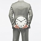 Businessman holding wall clock, rear view