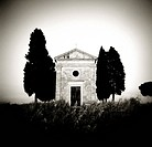 Image taken with a Holga medium format 120 film toy camera of old church of Vitaleta flanked by trees in silhouette, San Quirico d´Orcia, Tuscany, Ita...