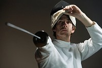 Man pointing fencing foil and lifting mask