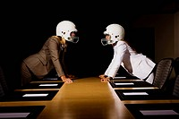Businesswomen in face_off wearing football helmets