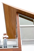 Couple hugging on balcony of modern house
