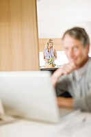 Woman in kitchen watching husband using laptop,