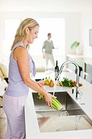 Woman washing celery in kitchen sink