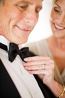 Close up of woman adjusting bowtie of man&#237;s tuxedo