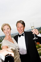 Couple in eveningwear drinking champagne on balcony