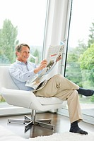 Man reading newspaper in living room